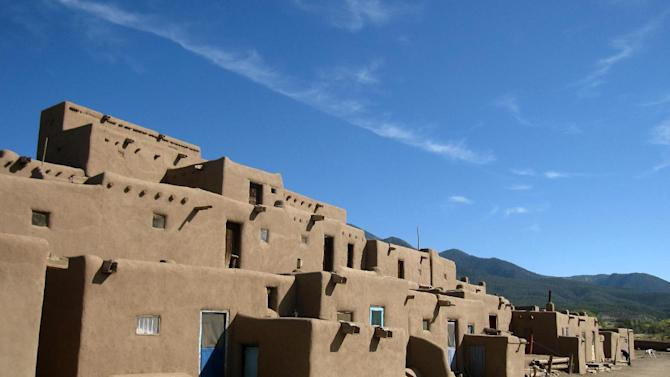 This October 2012 photo shows adobe dwellings at the Taos Pueblo in Taos, N.M., a UNESCO World Heritage site where the Taos native people have lived for 1,000 years. Tours of the pueblo describe the community's survival and challenges across the centuries. The picture-perfect dwellings are multi-level, often with ladders to reach upper floors and round ovens outside. (AP Photo/Beth Harpaz)