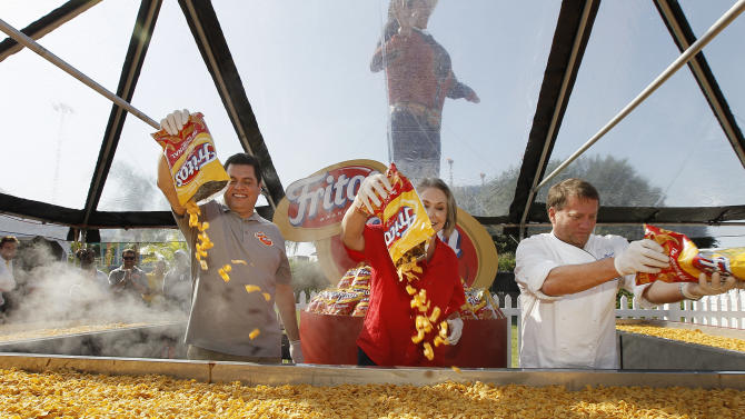 Tony Matta, vice president of marketing for Frito-Lay North America, Kaleta Doolin, daughter of Elmer Doolin, founder the Frito Company, and Jody Denton, executive chef at Frito-Lay North America, celebrate Fritos Corn Chips' 80th anniversary by helping build the World's Largest Fritos Chili Pie, weighing in at more than 1,300 pounds, at the State Fair of Texas in Dallas, Texas, Monday, October 1, 2012. (Photo by Brandon Wade/Invision for Frito-Lay/AP Images)