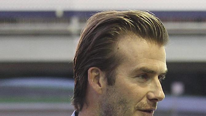 David Beckham arrives at the pit building before the start of the Singapore Formula One Grand Prix on the Marina Bay City Circuit in Singapore, Sunday, Sept. 22, 2013
