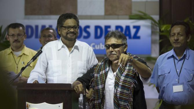 Jesus Santrich, member of the Revolutionary Armed Forces of Colombia (FARC), second from right, makes a joke before the start of a news conference, accompanied by fellow rebels Ivan Marquez, second from left, Yuri Camargo, far left, and Fidel Rondon, right, at the close of a round of peace talks with Colombia's government in Havana, Cuba, Friday, Aug. 22, 2014. Talks are expected to resume in September. (AP Photo/Ramon Espinosa)