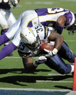 San Diego Chargers running back Mike Tolbert dives into the end zone for a touchdown as a Minnesota Vikings defender tries to stop him during the second half of a NFL football game Sunday, Sept. 11, 2011, in San Diego.  (AP Photo/Denis Poroy)