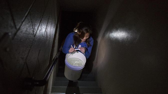 Grace Chow, 22, of New York, carries a large bucket of water on a twenty floor trip to help an older resident at Confucius Plaza in the Chinatown neighborhood of New York, Thursday, Nov. 1, 2012. In the wake of Superstorm Sandy, power outages have also meant loss of water for some buildings. Chow was volunteering with the New York United Dragon and Lion Dance group. (AP Photo/Craig Ruttle)