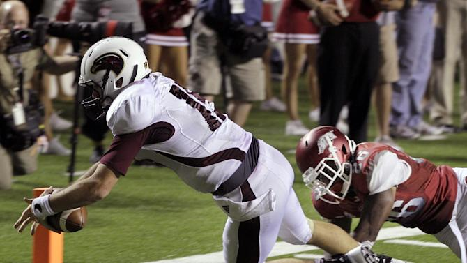 Louisiana Monroe quarterback Kolton Browning, left, carries the ball into the end zone past Arkansas safety Rohan Gaines (26) during overtime in an NCAA college football game in Little Rock, Ark., Saturday, Sept. 8, 2012. Louisiana-Monroe defeated Arkansas 34-31 in overtime. (AP Photo/Danny Johnston)