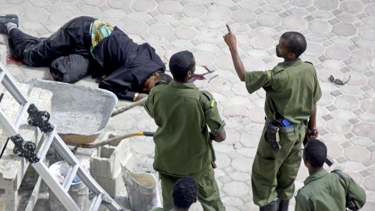 Somali soldiers stand by the body of a hotel worker, left, who died following two explosions which occurred near the gate of the temporary home of Somalia's new president Hassan Sheikh Mohamud, in Mogadishu, Somalia, Wednesday, Sept. 12, 2012. A day after the election of Somalia's new president, two explosions went off at the gate of his temporary residence which killed at least three people and wounded three others, a witness and officials said Wednesday. (AP Photo/Farah Abdi Warsameh)
