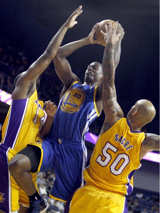 Golden State Warriors forward Harrison Barnes, center, splits the defense of Los Angeles Lakers forward Marcus Landry, left, and Lakers center Robert Sacre (50) in the fourth quarter during an NBA bas