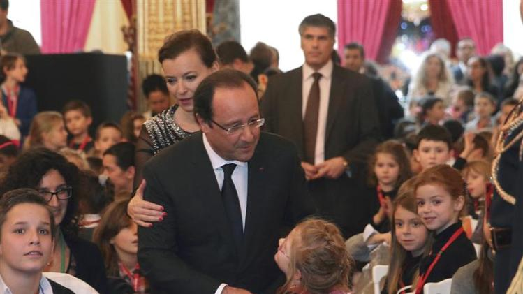 French President Hollande and his companion Trierweiler are greeted by children as they arrive at the Christmas party at the Elysee Palace, in Paris