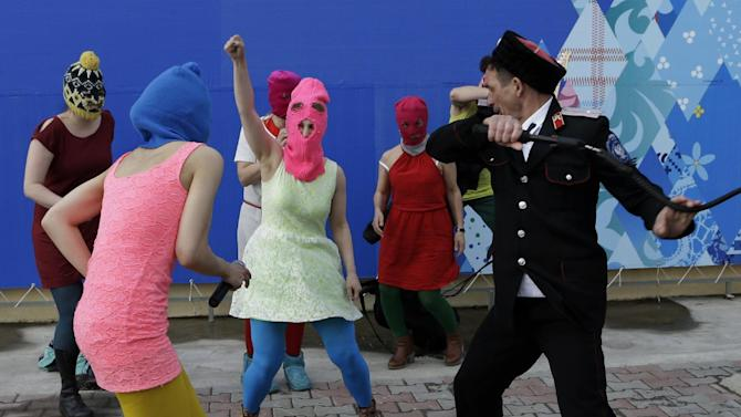 Members of the punk group Pussy Riot, including Nadezhda Tolokonnikova in the blue balaclava and Maria Alekhina in the pink balaclava, are attacked by Cossack militia in Sochi, Russia, on Wednesday, Feb. 19, 2014. The group had gathered in a downtown Sochi restaurant, about 30km (21miles) from where the Winter Olympics are being held. They ran out of the restaurant wearing brightly colored clothes and ski masks and were set upon by about a dozen Cossacks, who are used by police authorities in Russia to patrol the streets