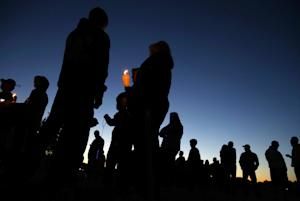 People hold candles as they gather for an anti-bullying…