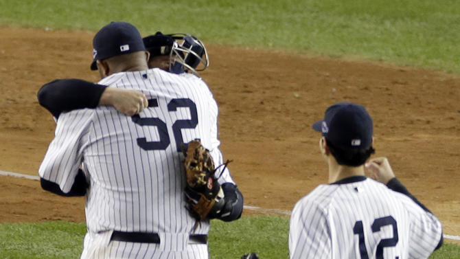 New York Yankees' pitcher CC Sabathia embraces catcher Russell Martin after winning Game 5 of  the American League division baseball series against the Baltimore Orioles, Friday, Oct. 12, 2012, in New York. The Yankees won the game 3-1 and advanced to the AL championship. Yankees' Eric Chavez approached at right. (AP Photo/Peter Morgan)