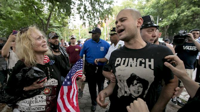 A man suspected by crowd of burning U.S. flag is aided by New York City NYPD officer following an anti-police protest in Fort Green Park in the Brooklyn Borough of New York