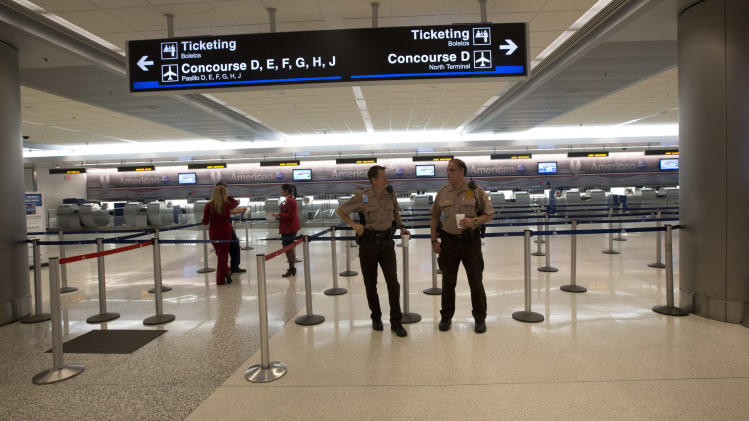 Police officers guard an empty check-in area at the American Airlines section of the Miami International Airport, Tuesday, April 16, 2013.  American Airlines says it has fixed an outage in its main reservations system that is disrupting travel for thousands of passengers whose flights have been delayed or canceled. But the airline expects to see flight delays and cancellations throughout the rest of the day.  (AP Photo/J Pat Carter)