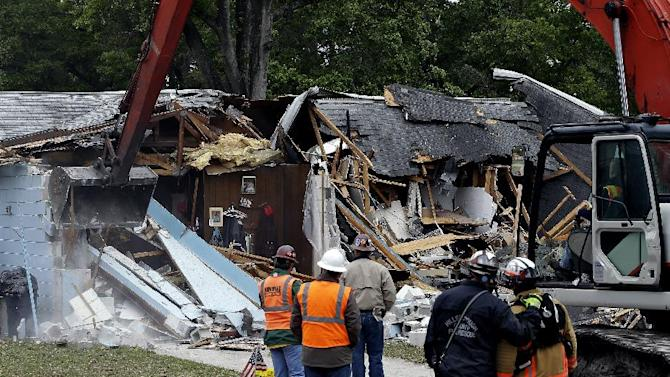 Demolition experts watch as the home of Jeff Bush, 37,  is destroyed Sunday, March 3, 2013, after a sinkhole opened up underneath it late Thursday evening swallowing Bush, 37, in Seffner, Fla. The 20-foot-wide opening of the sinkhole was almost covered by the house, and rescuers said there were no signs of life since the hole opened Thursday night. (AP Photo/Chris O'Meara)