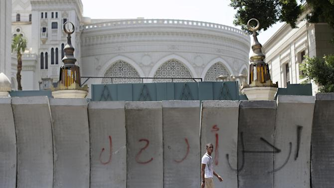 "FILE - In this Friday, June 28, 2013 file photo, an Egyptian man walks past graffiti Arabic writing that reads, ""leave"", on new concrete barricades erected ahead of mass protests against the country's Islamist President Mohammed Morsi that block the entrance of the presidential palace, in Cairo, Egypt. As the streets once again fill with protesters eager to oust the president and Islamists determined to keep him in power, Egyptians are preparing for the worst: days or weeks of urban chaos that could turn a loved one into a victim. Households already beset by power cuts, fuel shortages and rising prices are stocking up on goods in case the demonstrations drag on. Businesses near protest sites are closing until crowds subside. Fences, barricades and walls are going up near homes and key buildings. And local communities are organizing citizen patrols in case security breaks down. (AP Photo/Hassan Ammar, File)"