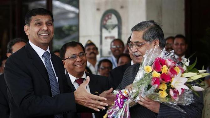 Raghuram Rajan (L), newly appointed governor of Reserve Bank of India (RBI) receives a bouquet from RBI deputy governor K C Chakrabarty after his arrival at the bank's headquarters in Mumbai September 4, 2013. REUTERS/Danish Siddiqui