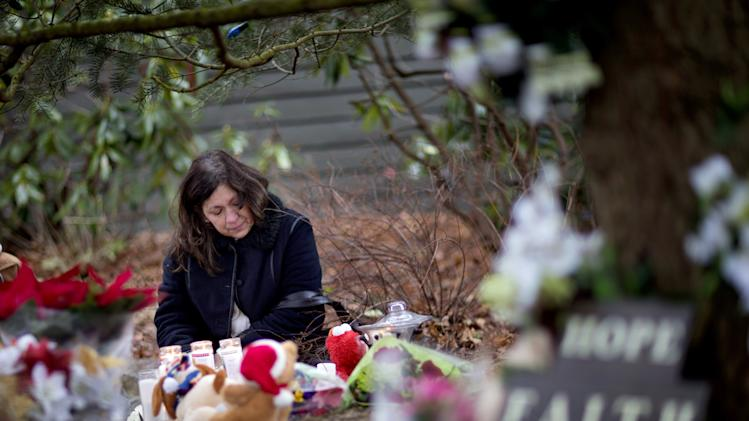 Dilma Steiner, of Newtown, Conn., visits a sidewalk memorial for the Sandy Hook Elementary School shooting victims, Sunday, Dec. 16, 2012, in Newtown, Conn. A gunman walked into the school Friday and opened fire, killing 26 people, including 20 children, before killing himself. (AP Photo/David Goldman)