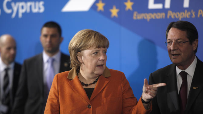 German Chancellor Angela Merkel gestures as Cyprus' main opposition Democratic Rally party leader Nicos Anastasiades, right, looks on, following a European People's Party (EEP) meeting in Cyprus' southern coastal resort of Limassol in an extraordinary summit on Friday, Jan. 11, 2013. Among the topics of discussion at the meeting hosted by the leader of Cyprus' main opposition Democratic Rally party Nicos Anastasiades was the EU budget. Anastasiades is currently leading opinion polls as the top contender ahead of the country's Feb. 17 presidential election. (AP Photo/Petros Karadjias)