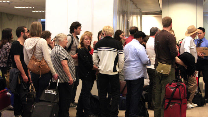 Passengers from the grounded Qantas A380 plane check-in on flights arranged to take them home on Friday Nov. 5, 2010 at the Changi International Airport in Singapore. Qantas grounded its Airbus A380 fleet after one of the superjumbo jets blew out an engine Thursday, shooting flames and raining large metal chunks before making a safe emergency landing in Singapore with 459 people aboard. (AP Photo/Wong Maye-E)
