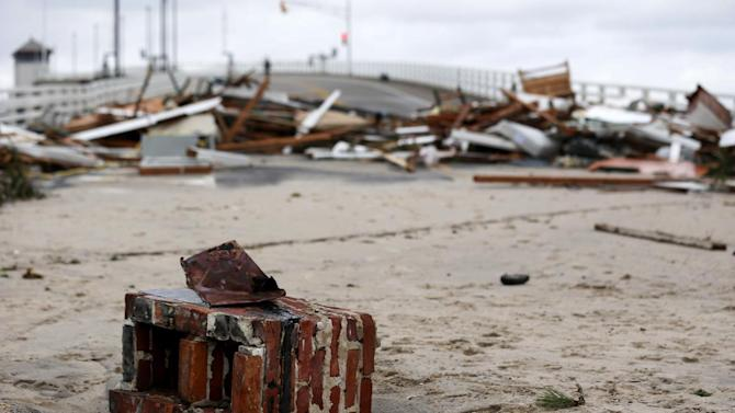 The remains of a chimney rest on the Mantoloking Bridge the morning after hybrid storm Sandy rolled through, Tuesday, Oct. 30, 2012, in Mantoloking, N.J. Sandy, the storm that made landfall Monday, caused multiple fatalities, halted mass transit and cut power to more than 6 million homes and businesses. (AP Photo/Julio Cortez)
