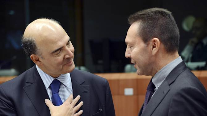 French Finance Minister Pierre Moscovici, left, speaks with Greek Finance Minister Yannis Stournaras during a meeting of eurogroup finance ministers in Brussels on Tuesday, Nov. 20, 2012. European Union officials will make a fresh try Tuesday to reaching a political accord on desperately needed bailout loans to Greece, an agreement that eluded them last week. (AP Photo/Thierry Charlier)