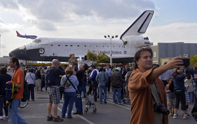Spectators gather around the Space Shuttle Endeavour before it is moved along city streets, Friday, Oct.12, 2012, in Los Angeles. Endeavour&#39;s two-day, 12-mile road trip to the California Science Center, where it will be put on display, kicked off early Friday. Rolled on a 160-wheeled carrier, it left from a hangar at the Los Angeles International Airport, passing diamond-shaped &quot;Shuttle Xing&quot; signs, and reached city streets about two hours later. (AP Photo/Mark J. Terrill)