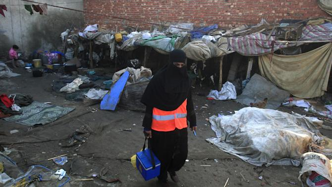A Pakistani female health worker visits Lahore's slums to administer the polio vaccine to infants on Wednesday, Dec. 19, 2012 in Pakistan. Gunmen shot dead a woman working on U.N.-backed polio vaccination efforts and her driver in northwestern Pakistan on Wednesday, officials said, raising the number of people killed in the last 48 hours who were part of the immunization drive. (AP Photo/K.M. Chaudary)