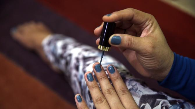 The fingernails of a transgender person are seen as she applies nail polish at her office in Banda Aceh