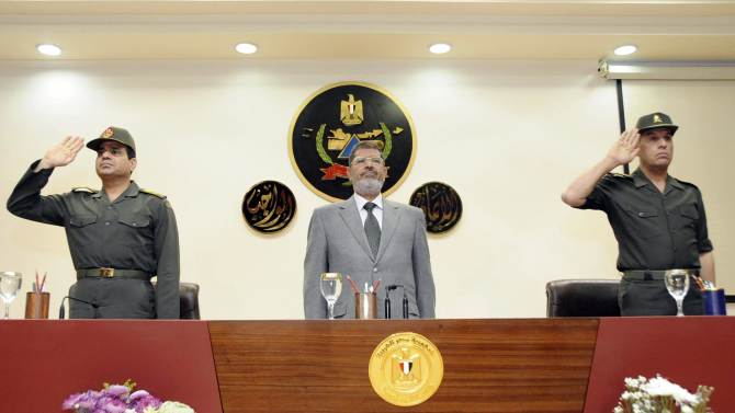 In this image released by the Egyptian Presidency, Egyptian President Mohammed Morsi, center, is seen with Minister of Defense, Abdel-Fattah el-Sissi, left, and an unidentified officer, during his visit to a military facility in Cairo, Egypt, Friday, March 22, 2013. Morsi confirmed his full confidence in the ability of members of the armed forces to face any challenges taking place in the country. (AP Photo/Egyptian Presidency)