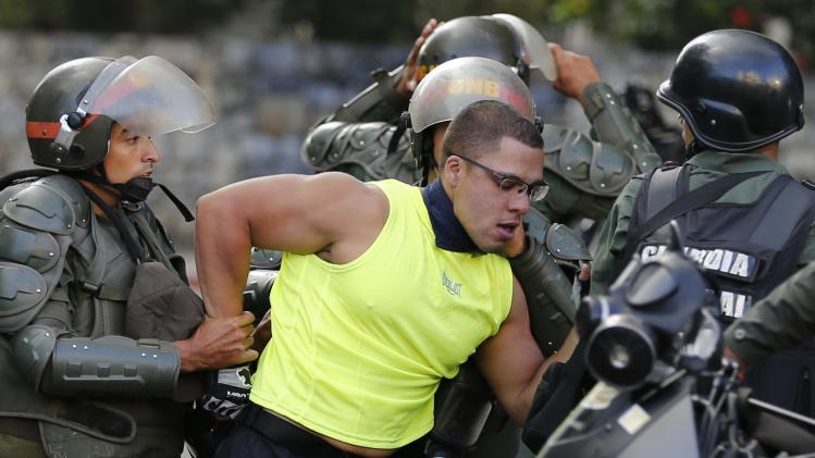 National guards transport an anti-government protester during clashes with police against Nicolas Maduro's government in Caracas