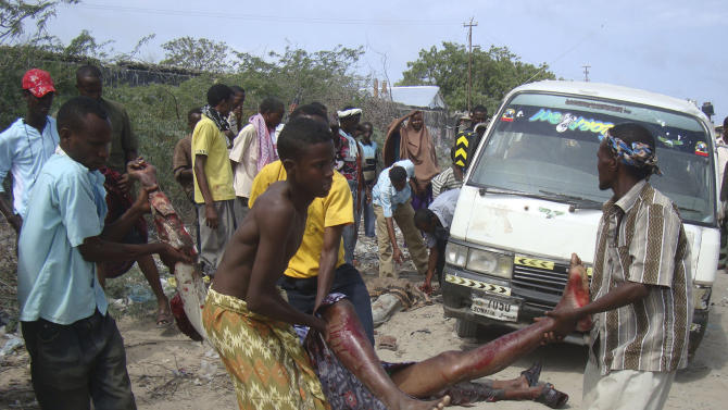Somalis carry a wounded civilian who was injured in a roadside bomb blast that missed African Union (AU) peacekeepers and struck a civilian transport truck, killing four civilians, in southern Mogadishu Somalia Tuesday June, 21, 2011(AP Photo/Farah Abdi Warsameh)