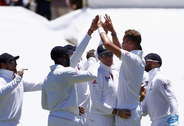 Team mates surround England's Broad after he combined with Swann to dismiss Australia's Watson during the first day's play of third Ashes cricket test match in Perth