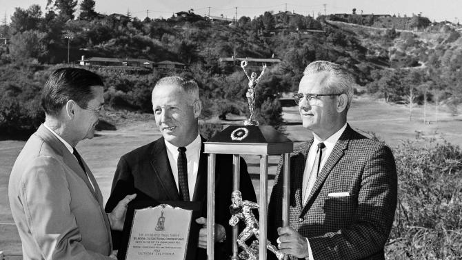 FILE - In this Dec. 27, 1962 file photo, The Associated Press trophy, symbolic of the national collegiate football championship, is presented in Pasadena, Calif., by AP sports writer Bob Myers, left, to Southern California head coach John McKay, center, and athletic director Jess Hill of Southern California. USC was named the No. 1 team in the final AP poll of the nation's sports writers and sportscasters.  (AP Photo/David Smith, File)