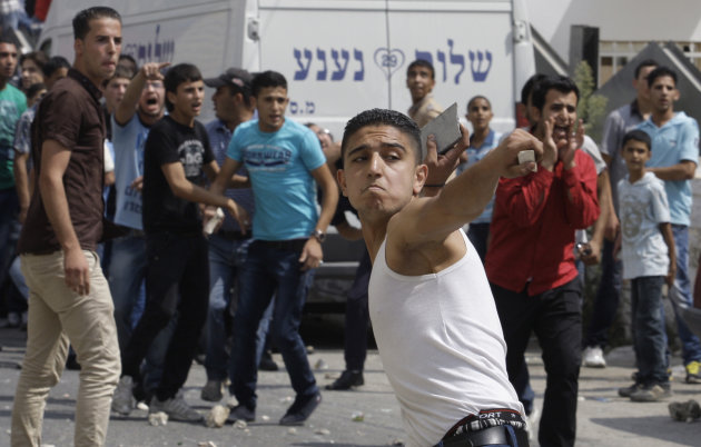Palestinian demonstrators throw stones towards Palestinian police during a protest near the municipality building in the West Bank city of Hebron, Monday, Sept. 10, 2012. Palestinian demonstrators fed up with high prices and unpaid salaries shuttered shops, halted traffic with burning tires and closed schools throughout the West Bank on Monday in the largest show of popular discontent with the governing Palestinian Authority in its 18-year history. (AP Photo/Nasser Shiyoukhi)