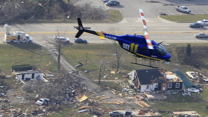 In this aerial photo, a television news helicopter flies over damaged homes Saturday, March 3, 2012, in Henryville, Indiana, after a tornado swept through the town Friday.   A string of violent storms demolished small towns in Indiana and cut off rural communities in Kentucky as an early season tornado outbreak killed more than 30 people, and the death toll rose as daylight broke on Saturday's search for survivors(AP Photo/Al Behrman)