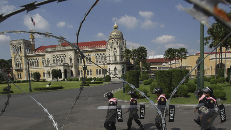Thai policemen patrol guard inside the compound of Government House in Bangkok, Friday, Nov. 23, 2012. Anti-government protesters are expected to show up in Bangkok on Saturday to demand an overthrow of the current government under the rule of Prime Minister Yingluck Shinawatra. (AP Photo/Sakchai Lalit)