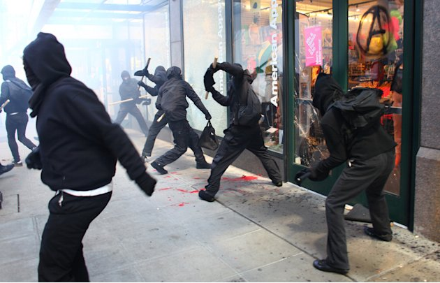 Protesters break windows on downtown businesses including American Apparel and NikeTown during a May Day rally on Tuesday, May 1, 2012 in downtown Seattle. About two dozen of the hundreds of protester