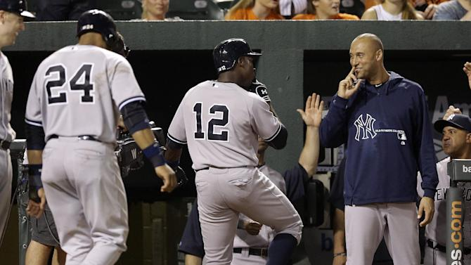 New York Yankees' Alfonso Soriano (12) and Derek Jeter, right, gestures after Soriano drove in teammate Robinson Cano (24) on a home run in the eighth inning of a baseball game against the Baltimore Orioles, Tuesday, Sept. 10, 2013, in Baltimore. New York won 7-5. (AP Photo/Patrick Semansky)