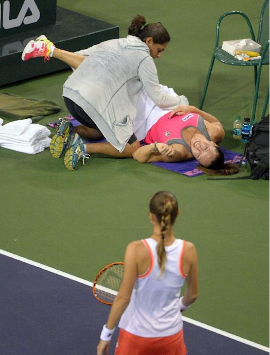 Jelena Jankovic, top, of Serbia, receives medical attention for her back as her opponent Magdalena Rybarikova, of Slovakia, looks on during their match at the BNP Paribas Open tennis tournament, Sunda