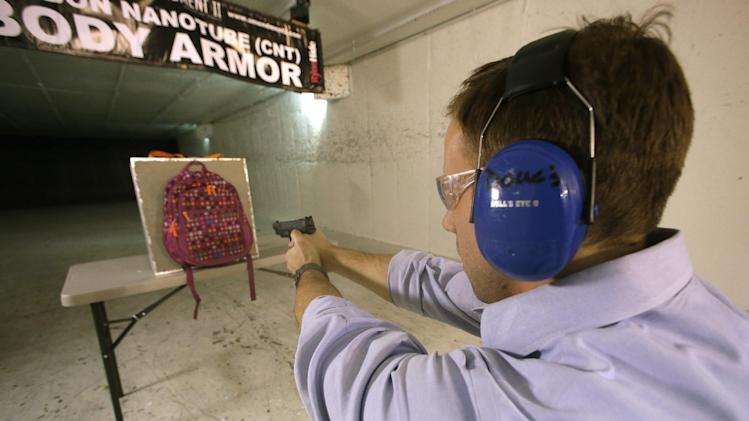 Rick Brand, Chief Operating Officer of Amendment II, shoots a 9 mm pistol into a children's backpack, left, fitted with an anti-ballistic insert, during a demonstration at a gun range, Wednesday, Dec. 19, 2012, in Taylorsville, Utah. Anxious parents reeling in the wake the Connecticut school shooting are fueling sales of armored backpacks for children, as firearms enthusiasts stock up on assault rifles nationwide amid fears of imminent gun control measures. At Amendment II, sales of children backpacks and armored inserts are up 300 percent. (AP Photo/Rick Bowmer)