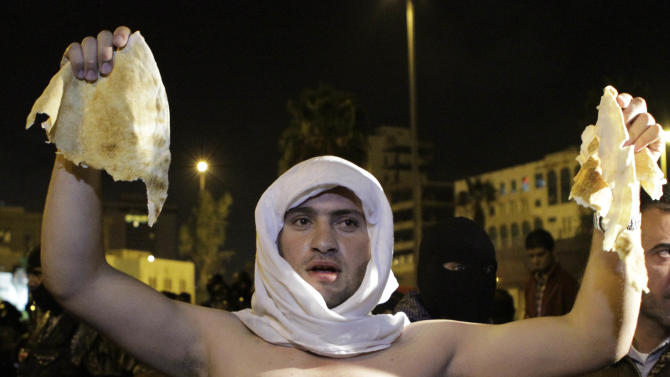A Jordanian man holds up a piece of bread during a demonstration in Amman following an announcement that Jordan would raise fuel prices, including a 53 percent hike on cooking gas, Tuesday, Nov. 13, 2012. (AP Photo/Raad Adayleh)