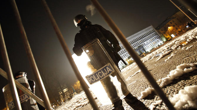 Riot police guard the parliament building during an anti government protest in Ljubljana, Slovenia, Friday, Feb. 8, 2013. Thousands gathered to protest against the Janez Jansa led government and their policies. (AP Photo/Darko Bandic)