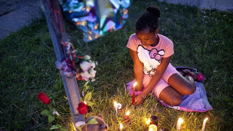 Jyonnaya Beauregard, 10, sits and plays with a candle by the memorial for Donald Arnold in Flint on July 9, 2014. A vigil was held for Arnold, who was killed Monday in a hit and run near the intersection of Martin Luther King Avenue and Ruth Avenue. Beauregard was a cousin of Arnold's. (AP Photo/The Flint Journal, Laura McDermott) LOCAL TELEVISION OUT; LOCAL INTERNET OUT