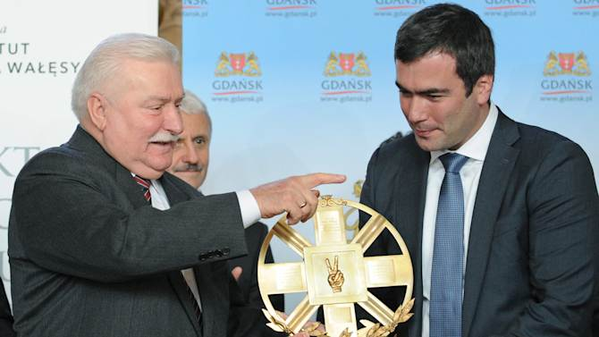 Solidarity founder and former Polish President Lech Walesa, left, gives his foundation's annual prize to the son of imprisoned Russian tycoon Mikhail Khodorkovsky, Pavel Khodorkovsky, in Gdansk, Poland, Sunday, Sept. 29, 2013. Walesa has given a US dollar 100,000 human rights award to Mikhail Khodorkovsky in recognition of his efforts to build a free economy and civil society. Khodorkovsky's son, Pavel, received the award for his father who remains imprisoned in Russia. (AP Photo/Alik Keplicz)