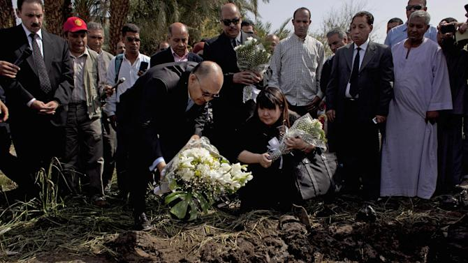 Japanese travel agent Okumura Hatsuko, bottom right, and Luxor's Govornor Ezzat Saad, bottom left, lay flowers to pay respect to Japanese tourists that died from a hot air balloon accident, in Luxor, Egypt, Wednesday, Feb. 27, 2013. A hot air balloon carrying tourists over Egypt's ancient city of Luxor caught fire on Tuesday, Feb. 26, 2013 and some passengers trying to escape the flames leaped to their deaths before the craft crashed in a sugar cane field. At least 19 tourists were killed in one of the world's deadliest ballooning accidents. (AP Photo/Nasser Nasser)