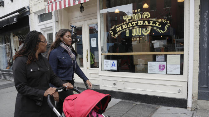 People walk past The Meatball Shop, Friday, Oct. 24, 2014, in the Greenwich Village neighborhood of New York. Dr. Craig Spencer, who has been diagnosed with Ebola, recently ate at the restaurant, which was temporarily closed Friday as a precaution. (AP Photo/Mark Lennihan)