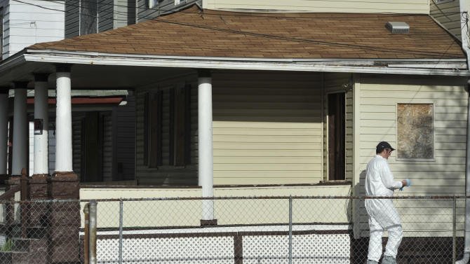 A member of the FBI evidence response team searches a house near the home where three women were held Wednesday, May 8, 2013, in Cleveland. A man was charged with four counts of kidnapping — covering all three captives and the daughter born to one of them while she was held — and three counts of rape against the three women.  (AP Photo/Roadell Hickman)