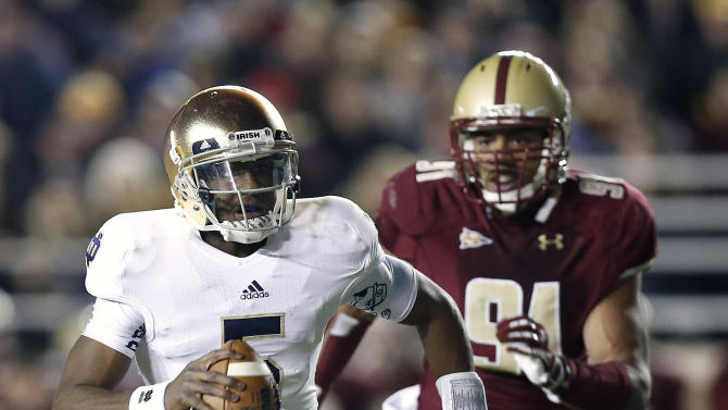 Notre Dame quarterback Everett Golson scrambles away from Boston College's Kasim Edebali during the first half of an NCAA college football game in Boston on Saturday, Nov. 10, 2012. (AP Photo/Winslow Townson)