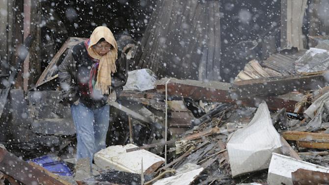Braving falling snow, a woman looks around destroyed factory in the rubble Wednesday, March 16, 2011 in Kesennuma, Miyagi Prefecture, five days after an earthquake-triggered tsunami devastated northeastern coastal towns in Japan. (AP Photo/Kyodo News) JAPAN OUT, MANDATORY CREDIT, NO LICENSING IN CHINA, HONG KONG, JAPAN, SOUTH KOREA AND FRANCE
