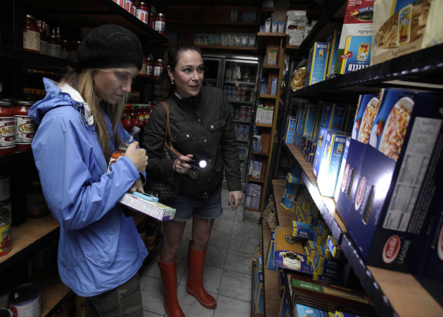 Two women shop for groceries by flashlight in the Tribeca neighborhood of New York, Tuesday, Oct. 30, 2012. ConEd cut power Moday to some neighborhoods served by underground lines as the advancing sto