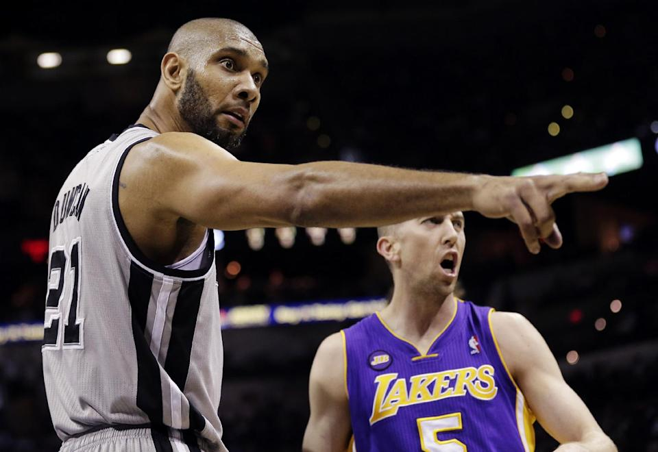 San Antonio Spurs' Tim Duncan (21) and Los Angeles Lakers' Steve Blake (5) argue a call during the first half of Game 1 of their first-round NBA playoff basketball series, Sunday, April 21, 2013, in San Antonio. (AP Photo/Eric Gay)