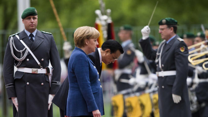 German Chancellor Angela Merkel, center foreground, and the Prime Minister of China,  Li Keqiang, center behind Merkel,  wait  during the welcoming ceremony prior to for a meeting at the chancellery in Berlin, Sunday, May 26, 2013.  (AP Photo/Markus Schreiber)